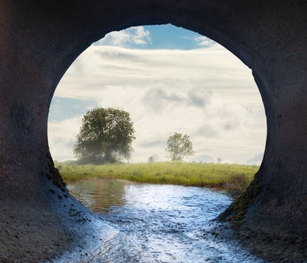 Vista of nature, seen through a water drainage pipe